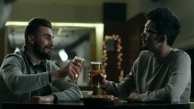 Male friends talking and drinking beer in pub