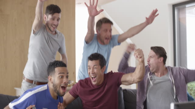 Male friends watching a match and celebrating