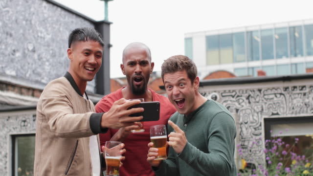 male friends watching sports on smartphone in an outdoor bar - kleine personengruppe stock-videos und b-roll-filmmaterial