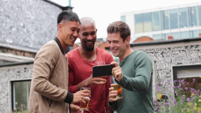 male friends watching video on smartphone in an outdoor bar - kleine personengruppe stock-videos und b-roll-filmmaterial
