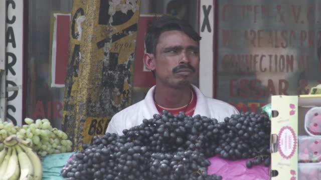 ws male fruit vendor by stall in street market selling grapes / delhi, delhi , india - solo un uomo di età media video stock e b–roll