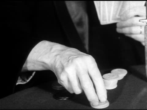 male gambler fingers on small stack of betting chips on poker table, other hand holding playing cards up bg, hand reaching forward, moving chips into... - gambling chip stock videos & royalty-free footage