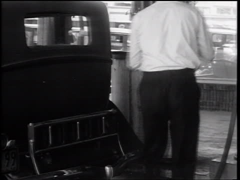 b/w 1932 male gas attendant hanging up hose near pump / man with bills approaching attendant - filling station attendant stock videos & royalty-free footage