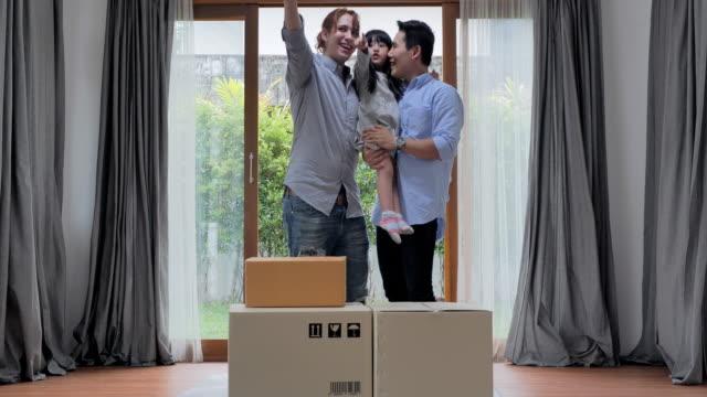 Mannelijk homopaar met aangenomen dochter verhuizen naar hun nieuwe thuis in hun nieuwe huis. Familie het dragen dozen in nieuw huis op bewegende dag. LGBT concept, nieuw huis concept.