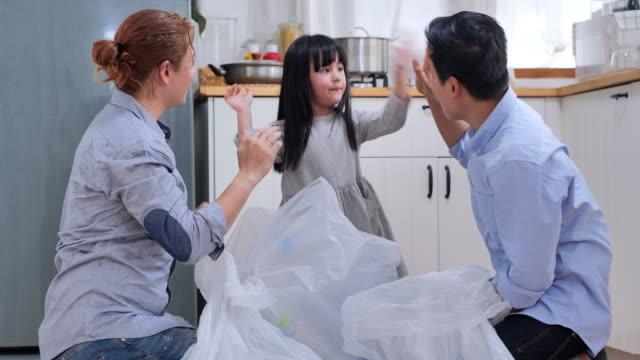 養子の娘を持つ男性ゲイ夫婦は、家庭ごみのリサイクル方法を教えています。チャリティー、人とエコロジーのコンセプト。リサイクルとエコロジー。生活習慣-生態学的教育と意識の概念.� - 再生利用点の映像素材/bロール
