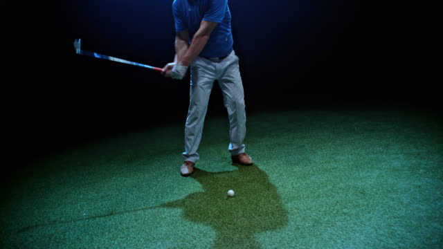 slo mo male golf player hitting the ball with his club at night - golfer stock videos & royalty-free footage