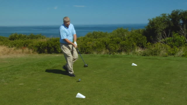 vídeos de stock, filmes e b-roll de ms, male golf trainer swinging club on golf course, north truro, massachusetts, usa - teeing off
