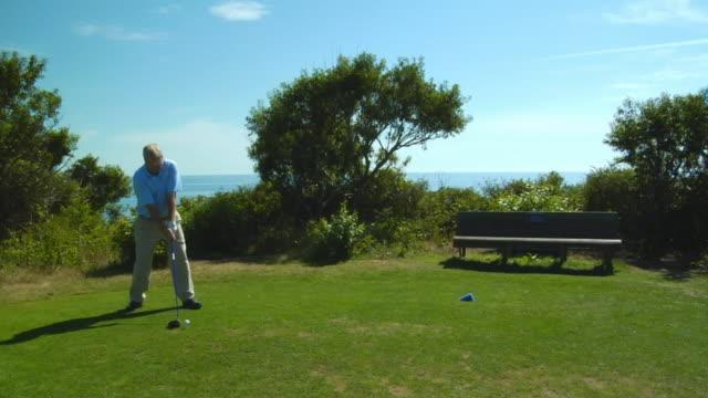 vídeos de stock e filmes b-roll de ms, male golf trainer swinging club on golf course, north truro, massachusetts, usa - golf