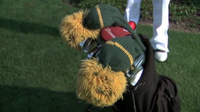 Male golfer legs in white pants behind golf bag filled w/ clubs two in knitted covers w/ pompom tips young adult male hand taking covered club out of...