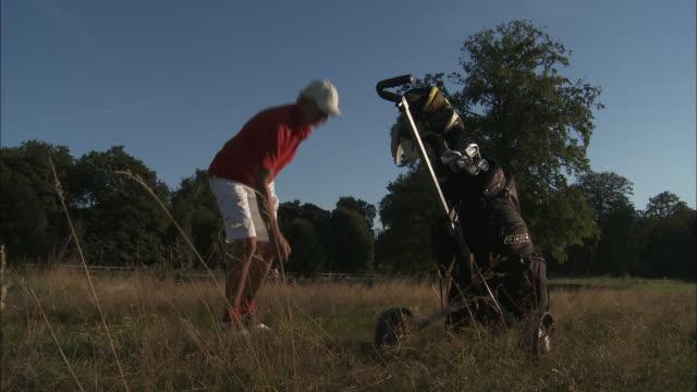 MS Male golfer pulling golf cart, Brussels, Belgium