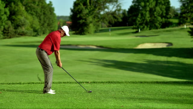 slo mo ws male golfer teeing off - golf swing stock videos & royalty-free footage