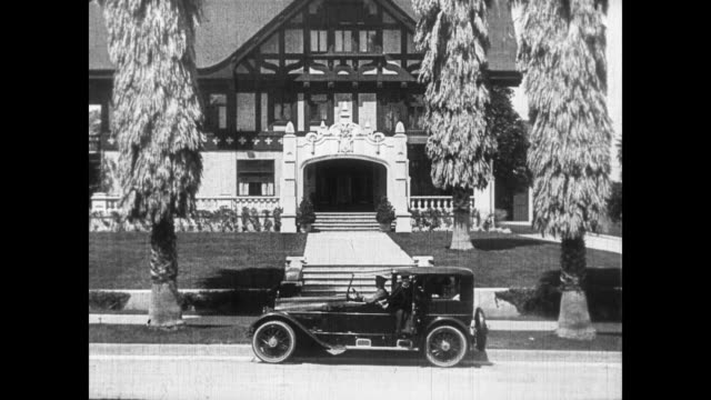 stockvideo's en b-roll-footage met 1922 male graduate (buster keaton) dropped off in front of mansion - afstudeer toga