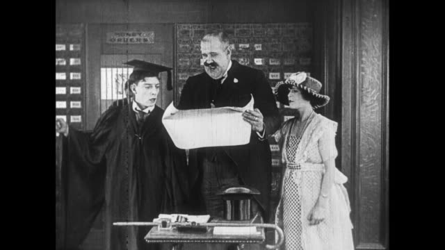 1922 male graduate (buster keaton) presents diploma to appreciative man - lupe stock-videos und b-roll-filmmaterial