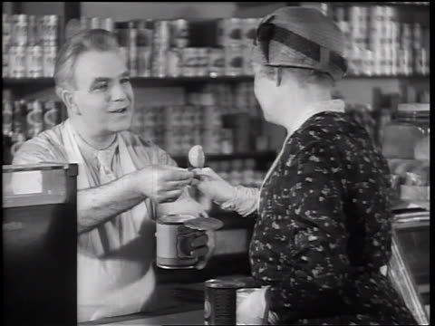 b/w 1933 male grocer giving canned peach slice to senior woman / woman trying peach + nodding - tin stock videos & royalty-free footage