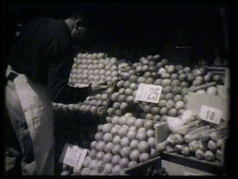 stockvideo's en b-roll-footage met male grocer picking through apples on fruit stand checking mcu hand tearing piece of molded bread apart in garbage can mcu hand w/ knife cutting... - kruidenier