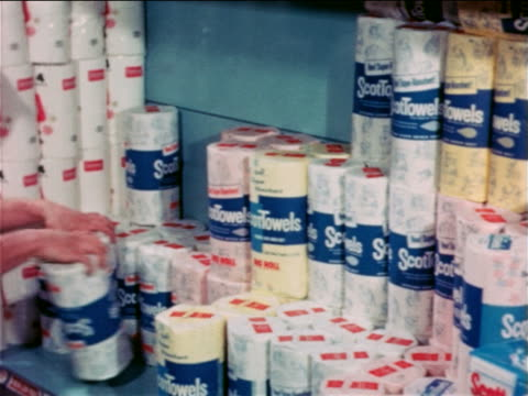 1965 male grocer's hands putting rolls of paper towels on shelf in grocery store / educational