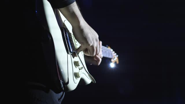 vidéos et rushes de guitariste masculin se produisant sur scène, close-up shot - un seul homme d'âge moyen