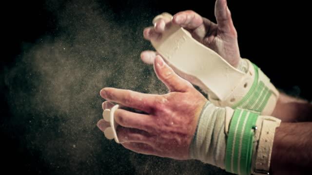 vídeos de stock, filmes e b-roll de slo mo ginasta bater palmas sua mão com tração juntos - giz equipamento esportivo