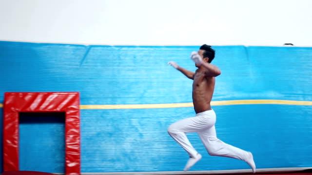 vídeos y material grabado en eventos de stock de gimnasta masculino haciendo un front handspring en la bóveda - magnesio