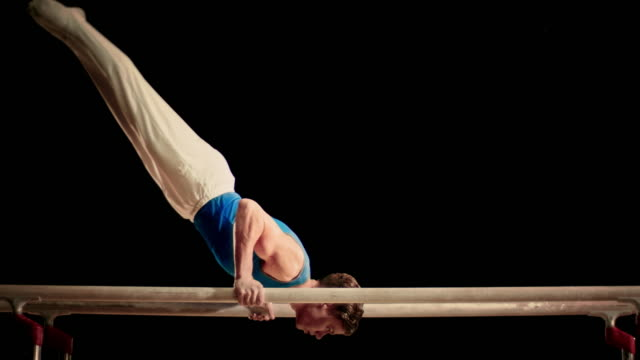 slo mo male gymnast doing a routine on parallel bars - gymnastics stock videos & royalty-free footage