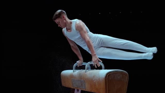 slo mo ld male gymnast doing circles on the pommel horse - akrobat bildbanksvideor och videomaterial från bakom kulisserna