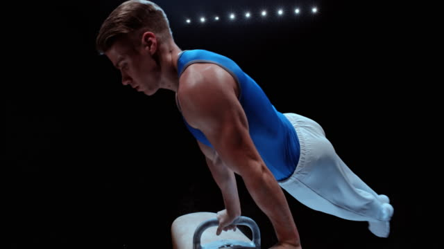 slo mo male gymnast doing rotation on pommel horse - turnen stock-videos und b-roll-filmmaterial