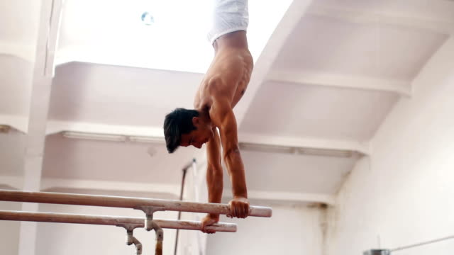 male gymnast exercise on parallel bar - stability stock videos & royalty-free footage