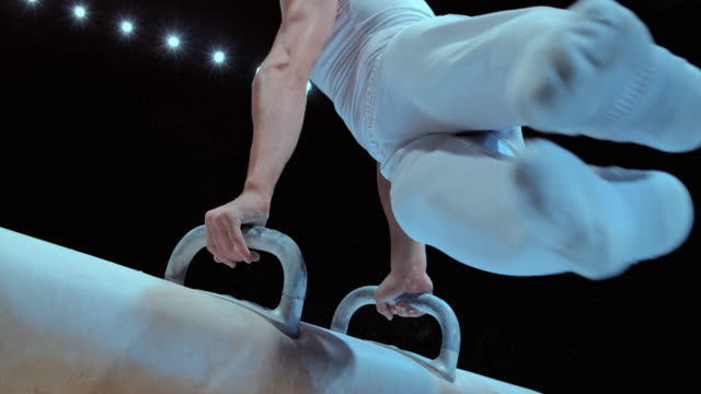 SLO MO Male gymnast in white outfit circling on the pommel horse