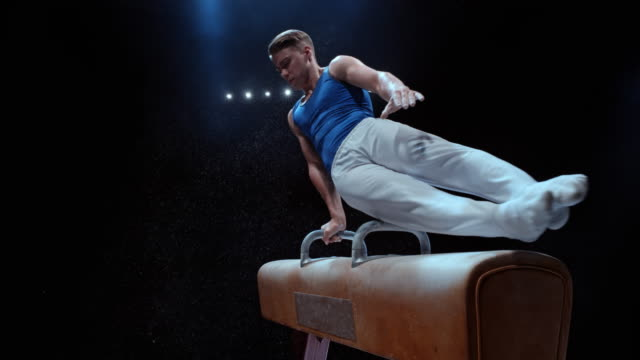 SLO MO Male gymnast rotating on a pommel horse