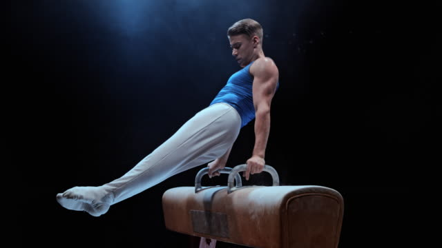 SLO MO LD Male gymnast rotating on a pommel horse