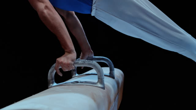 SLO MO Male gymnast rotating on the pommel horse