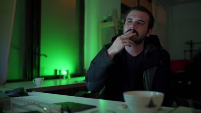 vídeos de stock, filmes e b-roll de hacker masculino comendo lanche e fumando em uma pausa de decodificar um programa - deep web