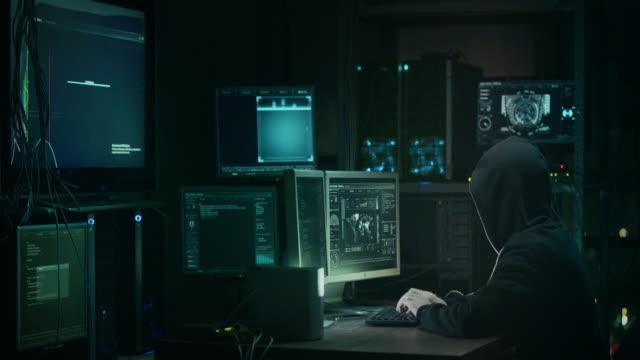 male hacker in a hood works on a computer with maps and data on display screens in a dark office room. - thief stock videos & royalty-free footage