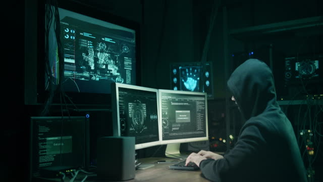 Male hacker in a hood works on a computer with maps and data on display screens in a dark office room.