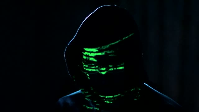 male hacker working on a computer while green code characters reflect on his face - aggressione video stock e b–roll