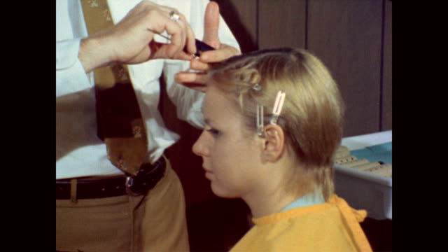 / male hair stylist talking with military woman on how she will wear her hair while on duty / fixes her hair / she puts on her hat and smiles into... - anno 1970 video stock e b–roll