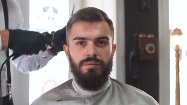 male hairdresser giving a haircut in his barber shop - barber chair stock videos & royalty-free footage