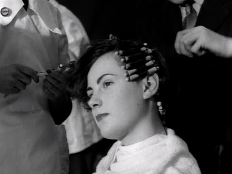 A male hairdresser styles a models hair during a hairdressing competition 1953