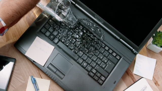slo mo ld male hand accidentally knocking over a glass of water and spilling it on his laptop - spilling stock videos and b-roll footage