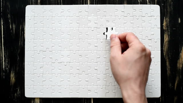 male hand adds white puzzle