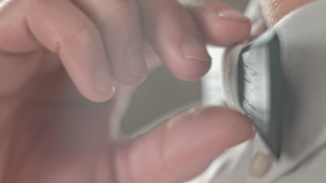 männliche hand anpassen einer hölzernen fliege um den hals - schleife stock-videos und b-roll-filmmaterial
