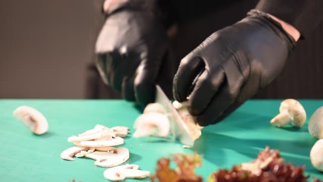 männliche hand nahaufnahme nimmt das messer und scheiben von reifen pilz auf einem schnitt - schneidebrett stock-videos und b-roll-filmmaterial