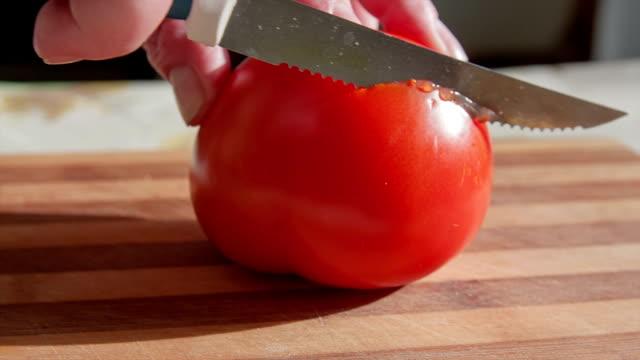 Kochen und Heimat Konzept-Nahaufnahme der männlichen hand Schneiden Tomate auf Schneidebrett mit scharfen Messer