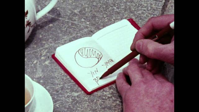 vídeos de stock, filmes e b-roll de cu male hand drawing yin yang symbol in notebook; 1973 - caderno de anotação