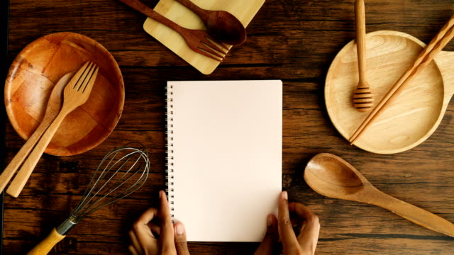 A male hand hold in recipe cooking book  paper  with cooking equipment on the wooden desk, top view and overhead shot use for blank template book mock up to add any text content for cuisine cooking scene concept