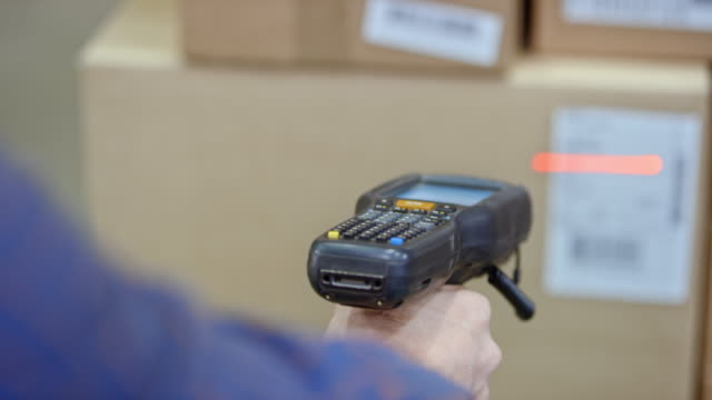 Male hand holding a scanner and scanning codes on the packages