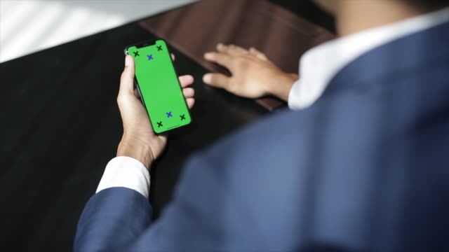 Male hand holding smart phone with green screen. Man using mobile phone while standing near window. Tapping on touchscreen, surfing the internet. close up