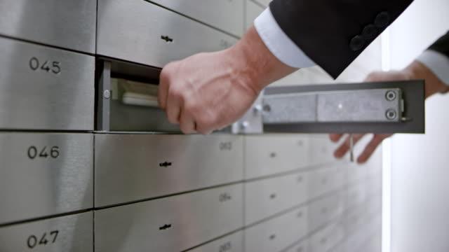 DS männlich Hand der Safe in den Tresorraum eine Box einfügen