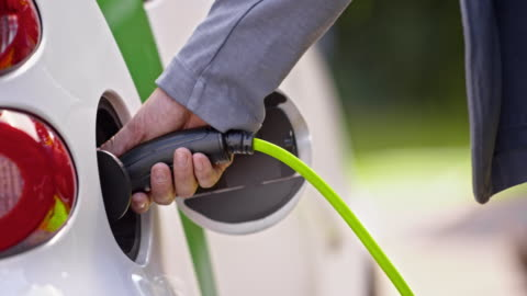 slo mo ds male hand inserting plug into electric car - environmental conservation stock videos & royalty-free footage