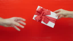 Male hand is giving present gift box to female hand. White gift box with red ribbon bow for Valentine's Day, Christmas or Birthday on red background. Man gives present to beloved woman, close up